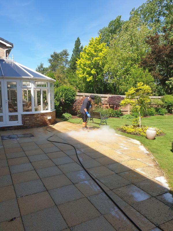 Pressure washing technician cleaning a garden patio
