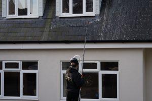 Applying a soft wash treatment to a slate roof.