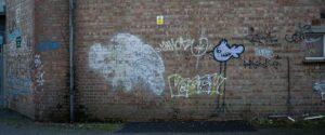 Multi coloured graffiti on a red brick wall in Oxford