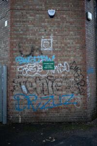 Lots of multi coloured graffiti on a brick wall