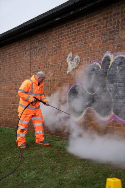 Stardust operative removing multi coloured graffiti from a brick wall