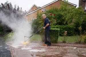 Stardust operative pressure washing a driveway